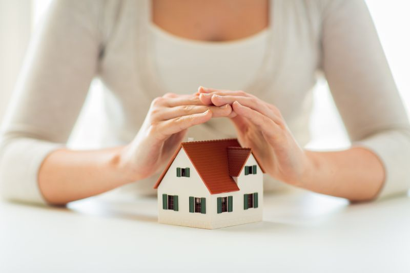 close up of hands protecting house or home model